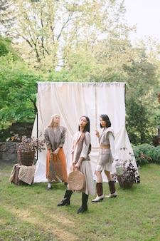 Drie mooie vrouwen die en zich in tuin bevinden kijken.