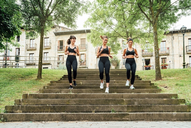 Drie mooie vrouwen rennen de trappen af van een park met veel stadsbomen, alle drie gekleed in zwarte sportkleding