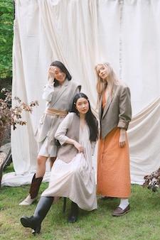 Drie mooie vrouwen staan, zitten en glimlachen in de tuin.