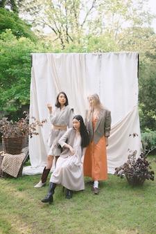 Drie mooie vrouwen staan, zitten en kijken in de tuin.