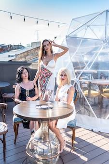 Drie mooie vrouwen vieren en chillen met champagne op terras