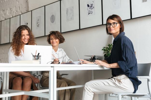 Drie mooie vrouwen zitten en werken bij de tafel