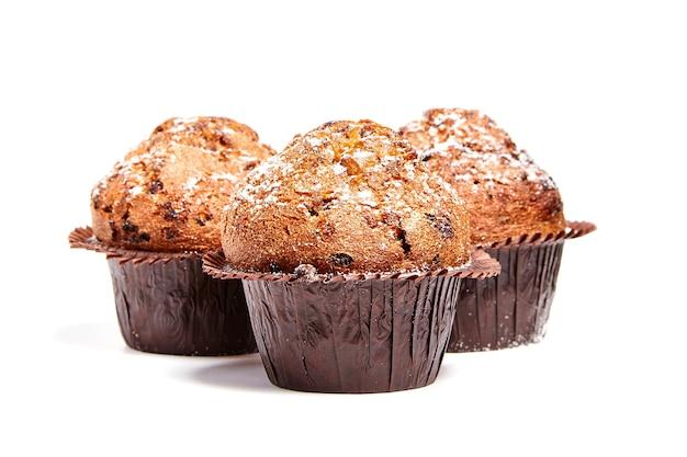 Drie muffins met geïsoleerde spaanders van chocolade