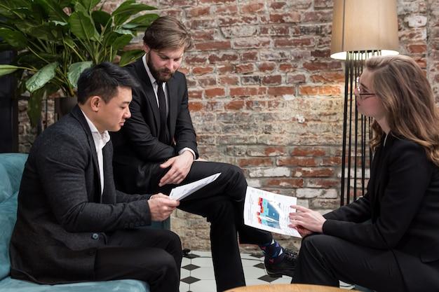 Drie multi-etnische zakenlieden overwegen een zakelijk contractaanbod