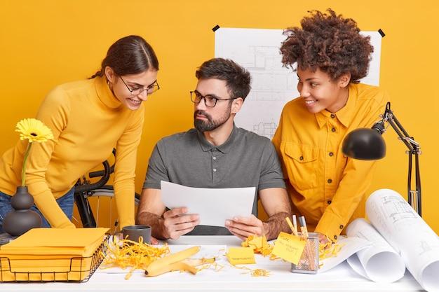 Drie multiculturele mensencollega's werken samen aan een architectonisch project, werken samen op de desktop met papieren en blauwdrukken, brainstormen over een werksessie