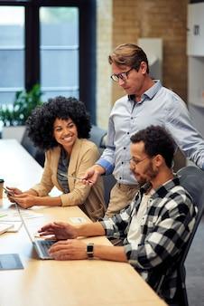 Drie multiraciale collega's werken samen in het moderne kantoor en kijken naar het laptopscherm en