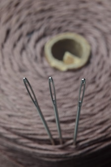 Drie naalden worden in een draadspoel gestoken. detailopname.