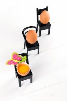 Drie natuurlijke eieren zitten op zwarte stoel met pasen-bloemdecoratie. minimale pasen concept idee. zakelijke pasen