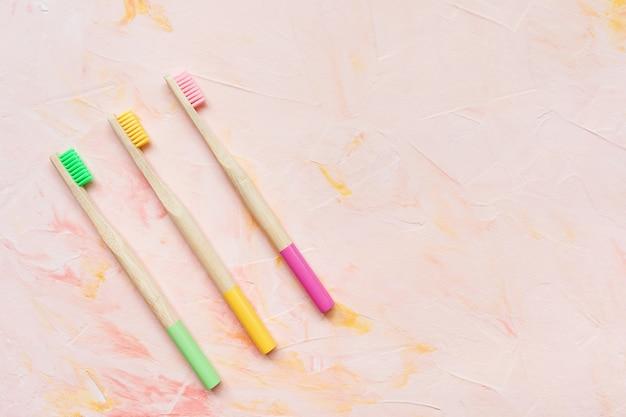 Drie natuurlijke houten bamboe tandenborstels. plasticvrij en afvalvrij concept. bovenaanzicht, roze backgroundon, kopie ruimte