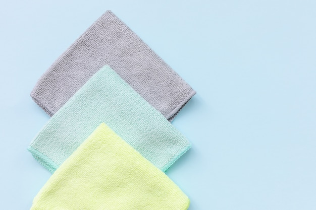Drie nieuwe gevouwen microfiber doek voor het reinigen over de blauwe achtergrond. handdoeken van microweefsel reinigen voor afstoffen en polijsten. huishoudelijke schoonmaak concept. close-up, kopieer ruimte