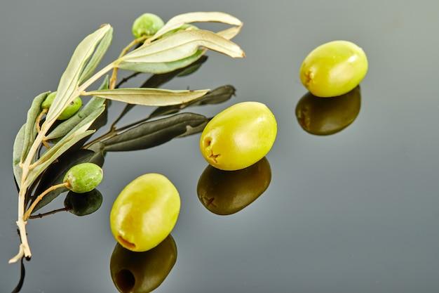 Drie olijven met olijfboomtak met vruchten die op een grijze achtergrond liggen