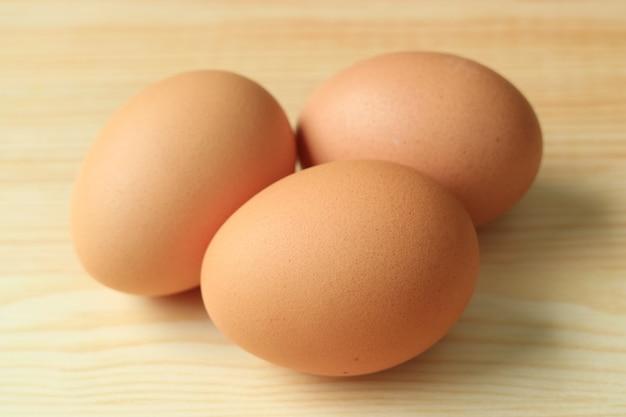Drie ongekookte verse kippeneieren die op de houten lijst worden geïsoleerd