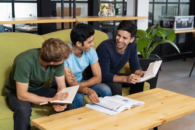 Drie ontspannen medestudenten studeren en chatten