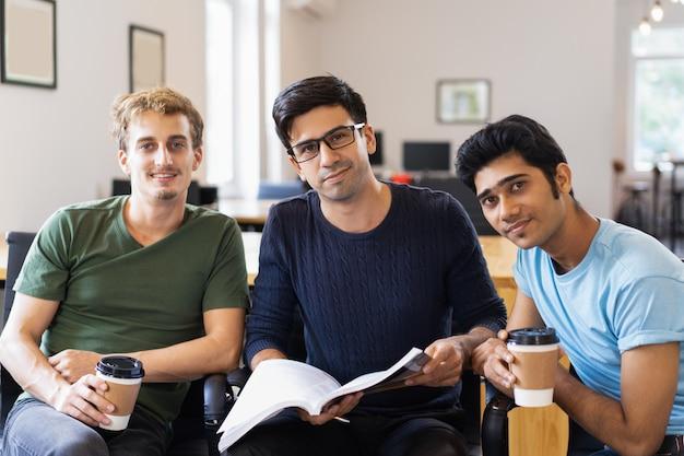 Drie ontspannen studenten studeren samen en drinken
