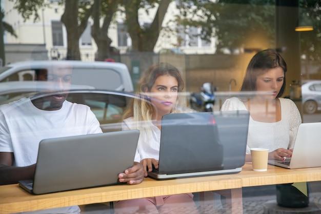 Drie ontwerpers werken aan laptops achter raam met reflectie