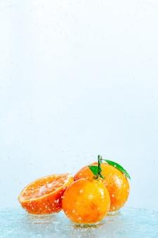 Drie oranje mandarijnen met een tak en bladeren staan in water op glas onder druppels water op wit