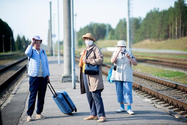 Drie oude hogere bejaarde vrouwen die op het perron wachten op trein en een gezichtsmasker dragen