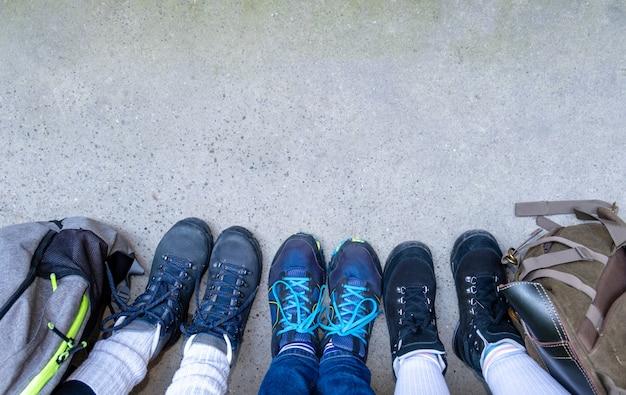 Drie paar benen in laarzen om te wandelen staan op de grijze stoep met rugzakken.