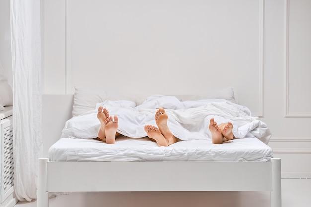 Drie paar vrouwelijke benen die onder de deken uitkomen. luie ochtend concept.