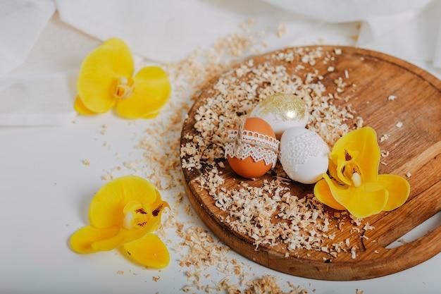 Drie paaseieren met gele orchideebloemen op houten achtergrond met rond zaagsel. paaseieren met kanten rand op houten snijplank. eieren decoratie. gouden paasei met glitters.