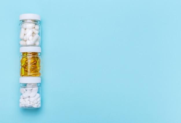 Drie pakketten met verschillende witte pillen en capsules op een blauwe achtergrond