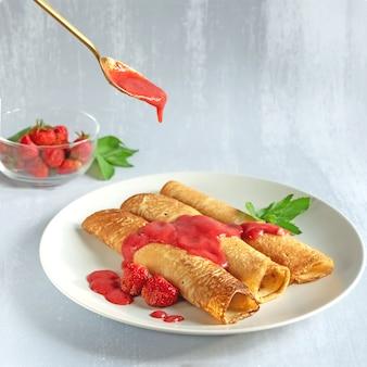 Drie pannenkoeken op een bord bedekt met aardbeiensaus, gegoten uit een lepel