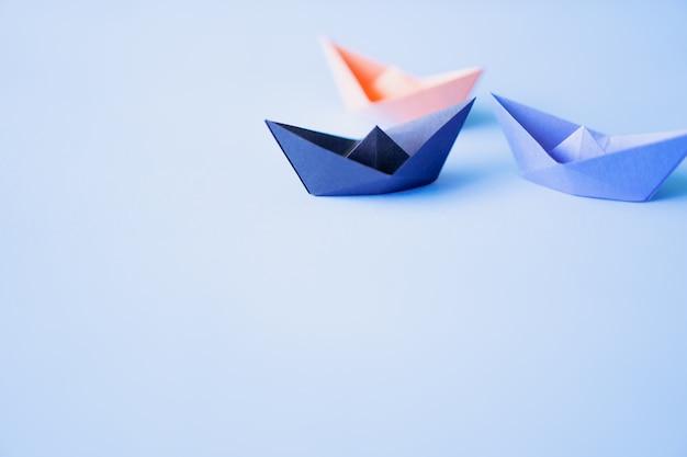 Drie papieren boot op schone achtergrond met kopie ruimte