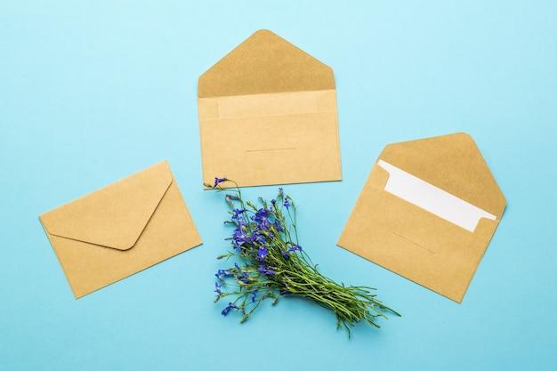 Drie papieren enveloppen voor brieven en een boeket bloemen op een blauwe achtergrond. plat leggen.