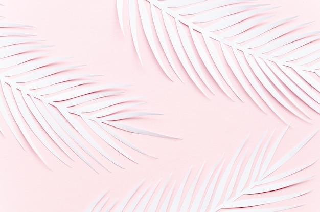 Drie papieren palmbladeren op roze tafel