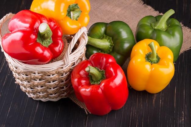 Drie paprika's op een houten achtergrond, het koken plantaardige salade