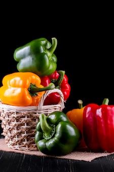 Drie paprika's op een houten lijst, die groentesalade koken