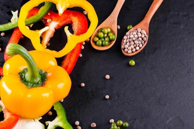 Drie paprika's op een houten oppervlak, plantaardige salade koken