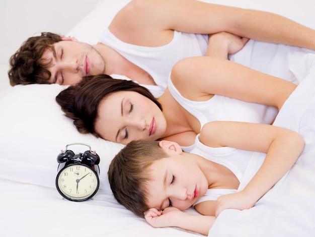 Drie personen van het jonge gezin slapen met wekker in de buurt van hun hoofd