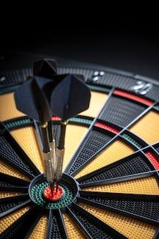 Drie pijltjes in bullseye van dartboard