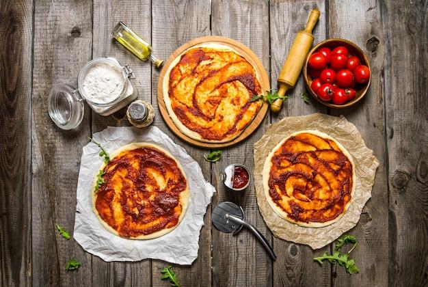 Drie pizza's verspreiden tomatensaus de ingrediënten.