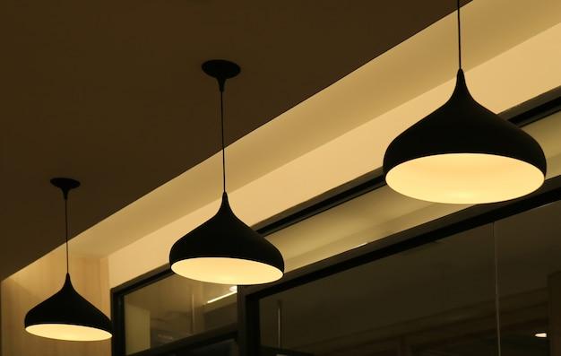 Drie plafondhangende lampenkappen die het warme licht verlichten