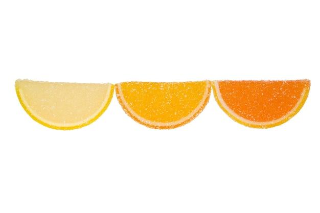 Drie plakjes gele en oranje marmelade bestrooid met kristalsuiker op een witte achtergrond
