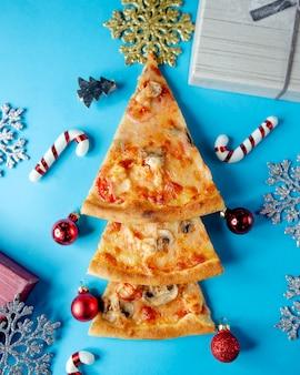 Drie plakjes pizza versierd in de vorm van een kerstboom