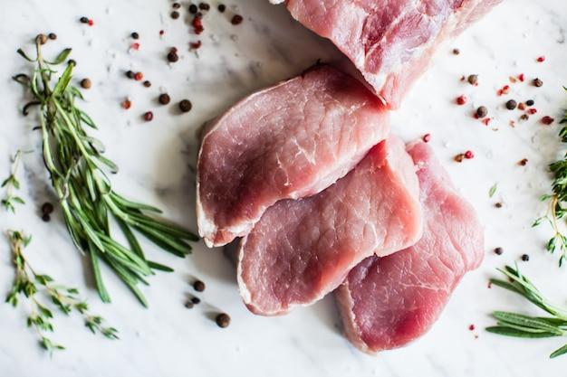 Drie plakjes rauwe varkenshaas met kruiden