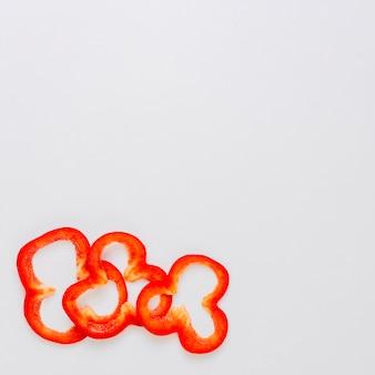 Drie plakjes rode paprika op de hoek van de witte achtergrond