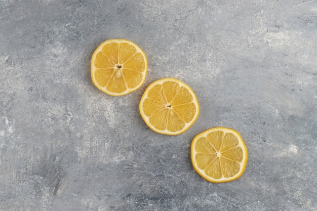 Drie plakjes zure citroen op een marmer.