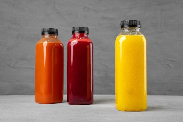 Drie plastic flessen met vers geperst sap op grijze achtergrond, exemplaarruimte