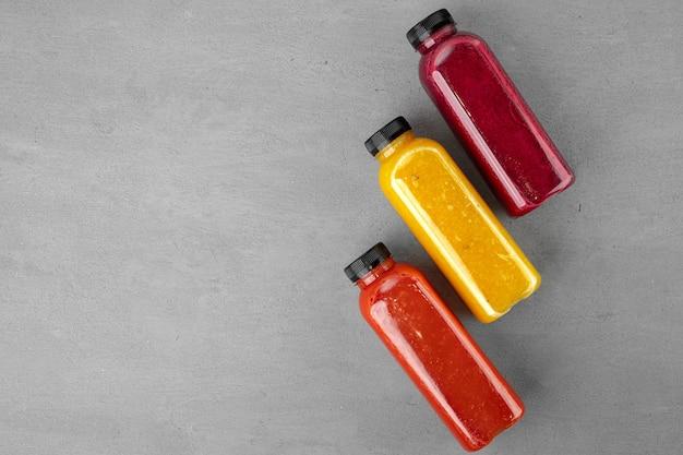 Drie plastic flessen met vers geperst sap op grijze ondergrond