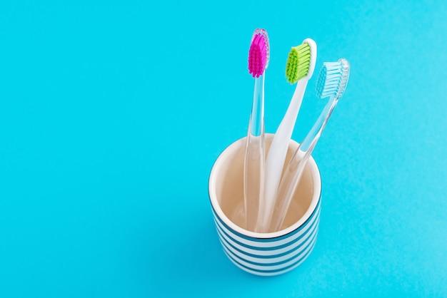 Drie plastic kleurrijke tandenborstels in glas op een blauwe achtergrond, sluiten omhoog