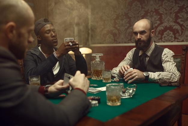 Drie pokerspelers met kaarten die in casino spelen. verslaving, gokhuis