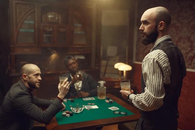 Drie pokerspelers zitten aan de tafel in het casino