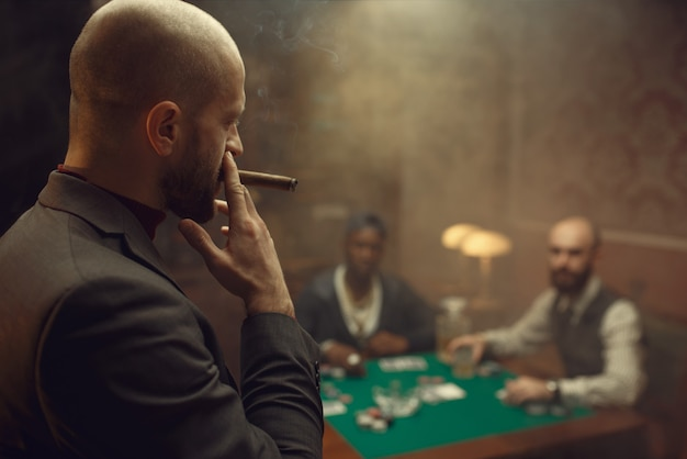Drie pokerspelers zitten aan de tafel Premium Foto