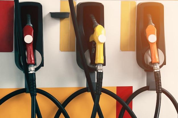 Drie pomp vullende pijpen in benzinestation