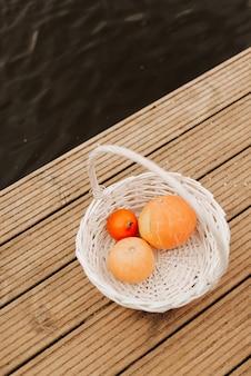 Drie pompoenen van verschillende grootte in een witte rieten mand herfst