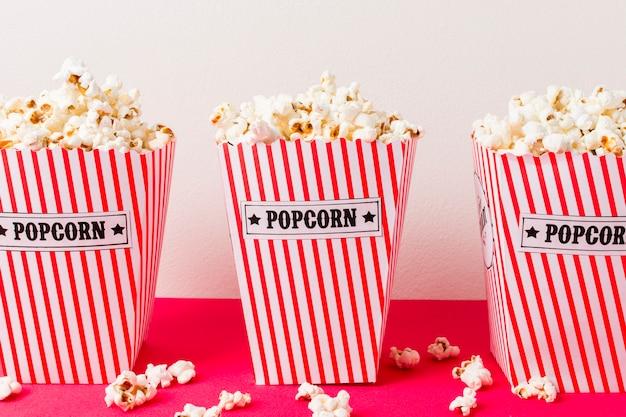 Drie popcorndoos die met popcorns op roze achtergrond wordt gevuld